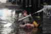 Κακοκαιρία «Μπάλλος»: Γυναίκα βγήκε με το κανό της στον πλημμυρισμένο δρόμο έξω από το σπίτι της